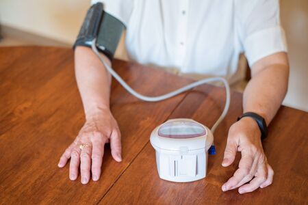 An elderly woman measures blood pressure with an electrical device. A pensioner uses a tonometer. Hands of an old woman.