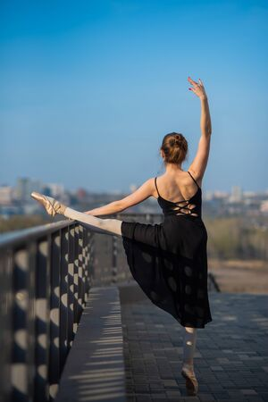 Ballerina in a tutu posing near the fence. Beautiful young woman in black dress and pointe dancing outside. Gorgeous ballerina demonstrates amazing stretching