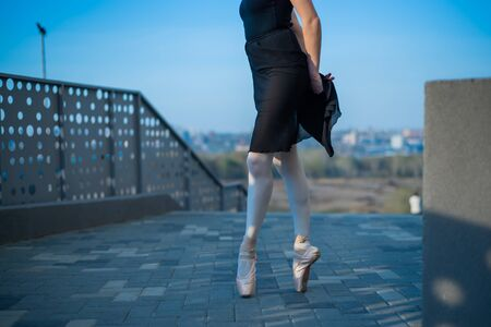 Ballerina in ballet legs in shoes and black tutu dancing by the fence. Beautiful young woman in black dress and pointe dancing outside. Gorgeous ballerina performing a dance outdoors. Close up.
