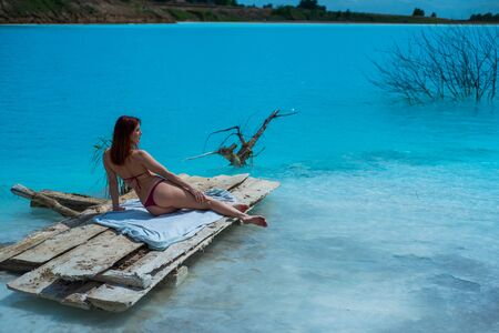 A beautiful red-haired woman in a seductive crimson bikini sits in front of an unusual turquoise lake. A miracle of nature, bright blue clear water. Ash dump, poisoned pond