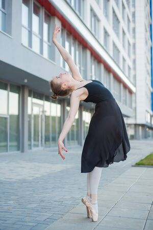 Ballerina in a tutu posing in front of a multi-storey residential building. Beautiful young woman in black dress and pointe shoes with incredible flexibility. Gorgeous ballerina performs an elegant ba 스톡 콘텐츠