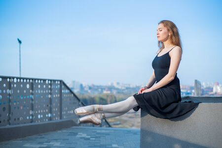 Ballerina in tutu posing sitting. Beautiful young woman in black dress and pointe dancing over city background. Portrait of a gorgeous ballerina performing a dance outdoors