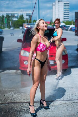 Luxury girls in seductive bikinis wash a car in a street car wash and water each other. Blonde and red-haired with beautiful figures wash a red car at a manual car wash. Self-care, dry cleaning salon 写真素材