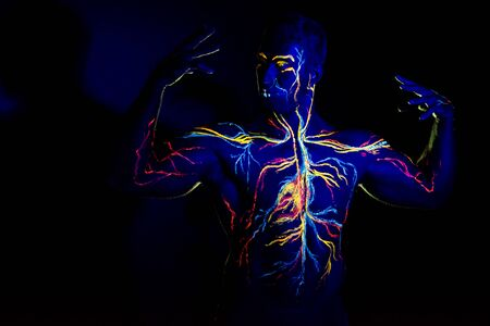 UV patterns body art of the circulatory system on a mans body. On the chest of a muscular athlete, veins and arteries are drawn with fluorescent dyes. The bodybuilder straightened the biceps.
