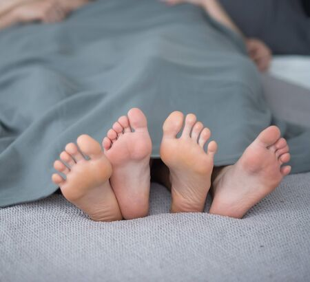 Close-up of male and female legs. The loving couple lies and embraces on the bed under a gray blanket. Light room 写真素材