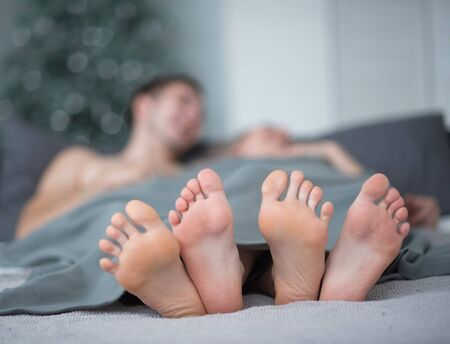Close-up of male and female legs. The loving couple lies and embraces on the bed under a gray blanket. Light room Banco de Imagens