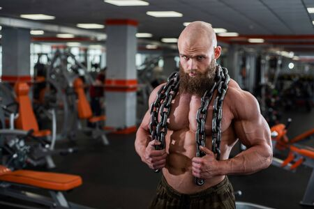 A bald, bearded bodybuilder with large relief muscles holds a heavy thick chain in his hands.