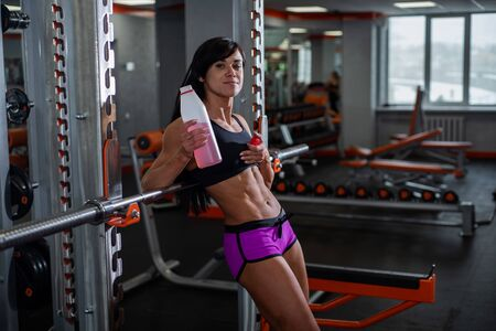 Young, beautiful, muscular athlete, resting and leaning on the barbell.