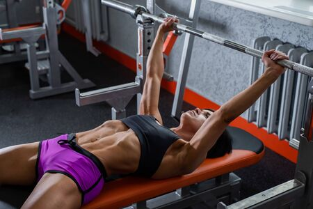 Powerful, strong, muscular girl in short shorts, performs bench press.
