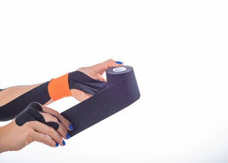 Physiotherapy for a diseased wrist. Alternative medicine. Adhesive tape for athletes with injuries. Support for an injured finger. Female hands on a white background hold a roll of kinesiotape 스톡 콘텐츠