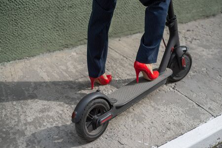 Young woman in formal wear on red hight heels is standing on electrical scooter. Close-up of female legs. A business woman in a trouser suit and red shoes moves around the city on an electric scooter 스톡 콘텐츠