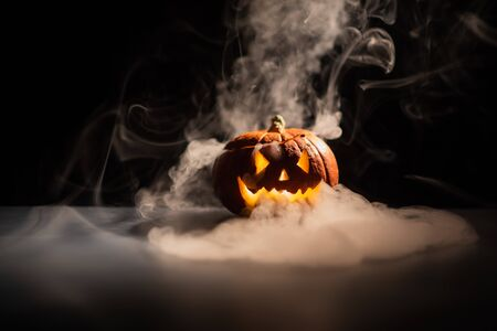 Halloween, orange pumpkin with a scary luminous face on a dark background. Gray thick smoke comes out. Close-up of jack-o'-lantern on the eve of all saints