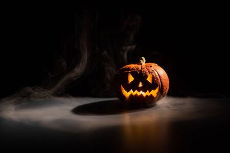 Halloween, orangefarbener Kürbis mit einem gruseligen leuchtenden Gesicht auf dunklem Hintergrund. Dicker grauer Rauch kommt heraus und breitet sich über den schwarzen Tisch aus. Eine Nahaufnahme einer Taschenlampe am Vorabend aller Heiligen