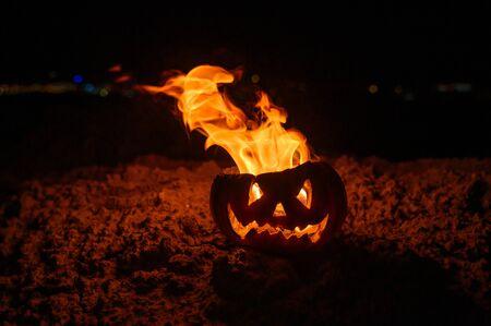 Langues de flammes dans une citrouille. jack-o-lantern en feu sur fond noir. Symbole d'Halloween au sol. La charité s'il-vous-plaît. Fermer