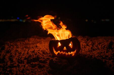 Tongues of flame in a pumpkin. jack-o-lantern on fire on a black background. Halloween symbol on the ground. Trick or treat. Close up