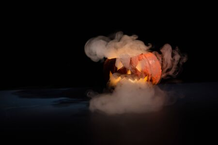Halloween, orange pumpkin with a scary luminous face on a dark background. Thick gray smoke comes out and spreads across the black table. A close-up of a flashlight on the eve of all the saints