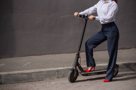 A red-haired girl in a white shirt drives an electric scooter along the wall. A business woman in a trouser suit and red high heels rides around the city in a modern car. dress code in the office