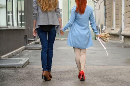 Paseo. Dos amigas caminan por la calle cogidos de la mano. Las espaldas de dos hermosas mujeres en un paseo con un ramo de flores secas. cosas arrugadas