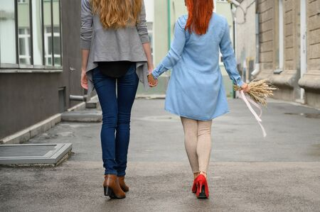 Stroll. Two girlfriends are walking along the street holding hands. The backs of two beautiful women on a walk with a bouquet of dried flowers. crumpled things Stock Photo