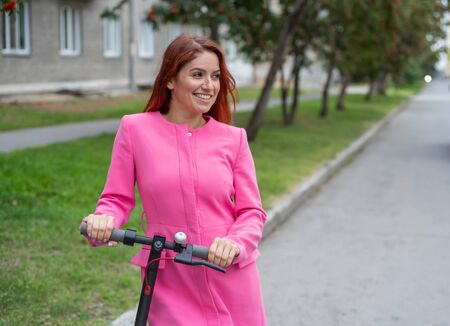 A red-haired young woman in ripped jeans and high-heeled sandals rides an electric scooter on the road. A girl in a pink jacket quickly moves around the city on a convenient electric transport.