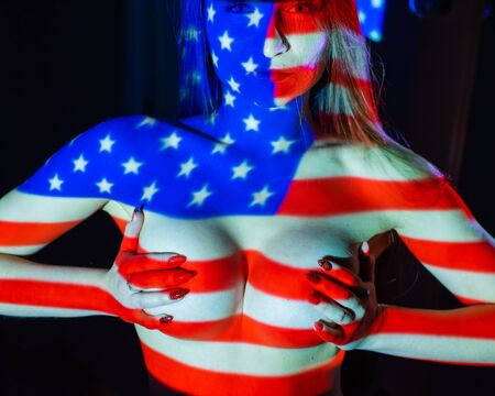 Projection of the flag of the United States of America on a beautiful naked girl. Covers a large female breast with her hands. Dark background. Banque d'images - 131313284
