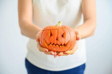 A woman in a white blouse holds a pumpkin for Halloween. Close-up of female hands with a lantern jack on a white background on the eve of All Saints. foreground. Trick or treat. Scary grimace. Standard-Bild