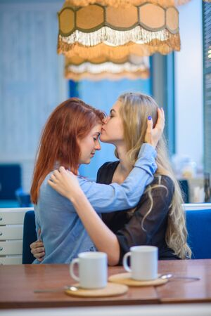 Same-sex relationships. Happy lesbian couple sitting in a cafe. Girls gently hold hands and drink coffee. Embrace of loving women. LGBT. Two best friends in cafe. Standard-Bild