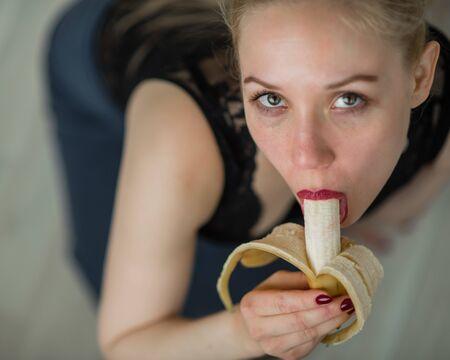Adult European girl sexually licks and sucks a big banana. Fantasies about oral sex. Face close-up. Banque d'images - 131313894