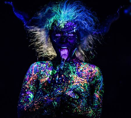 The girl in the image of the devil, contact lenses and horns. Woman paints her tongue in ultraviolet paint. fluorescent powder. Body art glowing in ultraviolet light. Stars in the eyes.