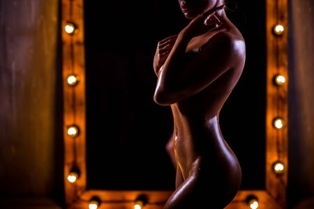 A young, naked, Caucasian girl with a very slender figure poses against a large mirror with lights in the loft style. The skin is oiled and shiny. Sexy tan. Banque d'images - 131313898