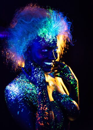 Body art and contact lenses glowing in ultraviolet light. Woman smiling, painted in fluorescent powder. Stars in the eyes