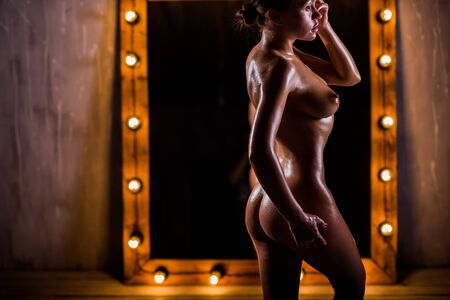 A young, naked, Caucasian girl with a very slender figure poses against a large mirror with lights in the loft style. The skin is oiled and shiny. Sexy tan. Banque d'images - 131314690