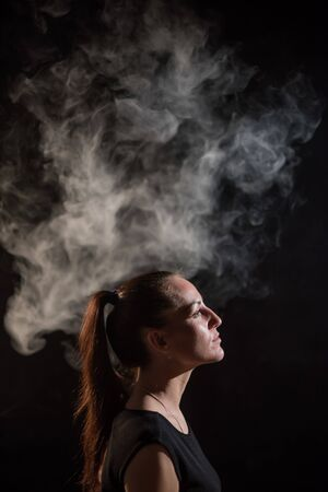 The brunette smokes an electronic cigarette on a black background, releases thick smoke from her mouth. Portrait of a woman smoking a vape, hovering. Banque d'images