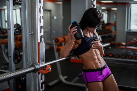 Young, beautiful, muscular athlete, resting and leaning on the bar. Shows your trained belly, Beautiful abs cubes. gym