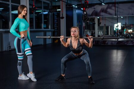 Young athletic girl doing barbell squats in the gym under the supervision of a trainer. A female coach teaches a ward to squat with a bar. Personal training. Exercises on the buttocks. Фото со стока