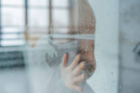 Young woman, posing behind transparent glass covered by water drops. melancholy and sad female portrait. Blonde in a white t-shirt touches the glass with drops in the shower room Banque d'images - 131315407