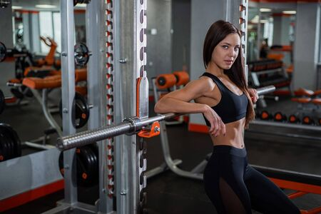 Young, beautiful, muscular athlete, resting and leaning on the barbell. gym