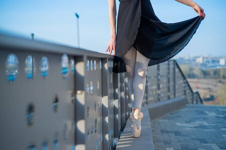 Ballerina in ballet legs in shoes and black tutu dancing by the fence. Beautiful young woman in black dress and pointe dancing outside. Gorgeous ballerina performing a dance outdoors. Close up