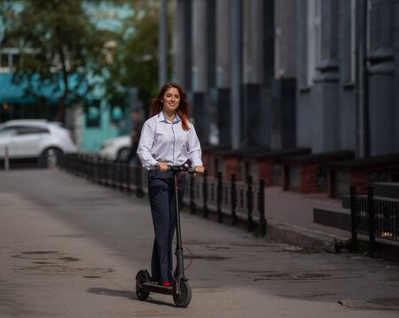 A red-haired girl in a white shirt drives an electric scooter along the wall. A business woman in a trouser suit and red high heels rides around the city in a modern car. dress code in the office.