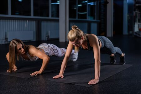 Female trainer teaches ward to do push-ups correctly. Beautiful woman trainer makes sure that her client, a young blonde, performs the exercises correctly. Personal training in the dark gym.