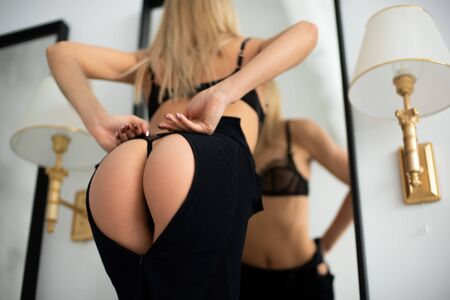The European girl seductively puts on a black skirt on a beautiful sports ass, the dress takes the shape of a heart. Zip
