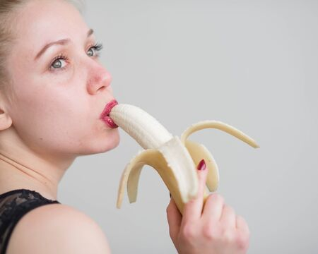 A girl with long blond hair sexually licks a big yellow banana with her tongue. Is oral sex Banque d'images - 131315980