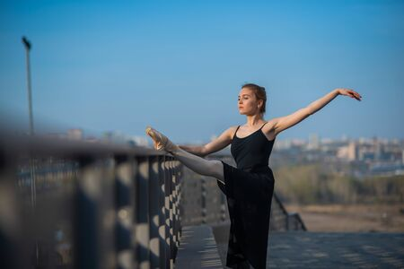 Ballerina in a tutu posing near the fence. Beautiful young woman in black dress and pointe dancing outside. Gorgeous ballerina demonstrates amazing stretching. Stock Photo