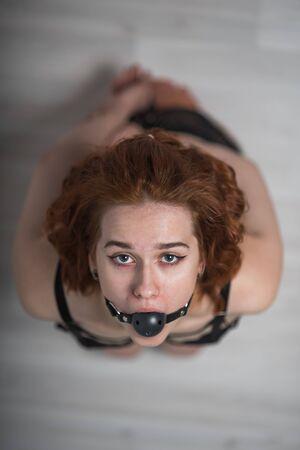 Niewolnictwo w społeczeństwie. Dziewczyna klęczy z kneblem w ustach. Zabawka seksualna. Niewolnictwo kobiet. Strój niewolnika do grania w gry. Przerażony niewolnik. Czarna skóra z kneblem. Przestraszony zakładnik Zdjęcie Seryjne