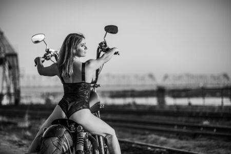 Red-haired woman in sexy lingerie in high heels sits on a motorcycle. Attractive red-haired girl sits on a motorcycle at sunset