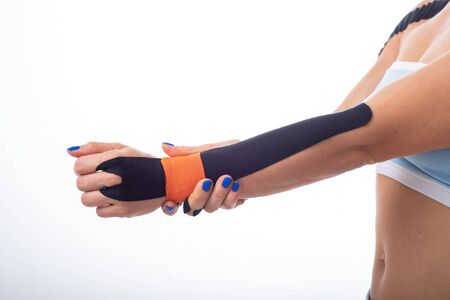 A female athlete puts a kineziotape on her wrist. Kineziology, alternative treatment for injuries of joints and tendons. Physiotherapy of chronic inflammation of the joints of a womans arm.