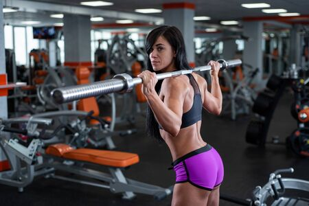 A strong, muscular dark-haired girl performs squats with barbell. Gym