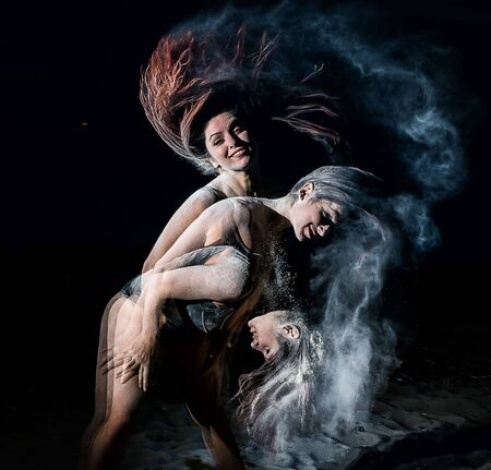 Three phases of a womans movement while dancing with flour. Ballerina dancing in white talcum powder clubs on a night beach. Female dancer action and motion in mixed and strobe light on black