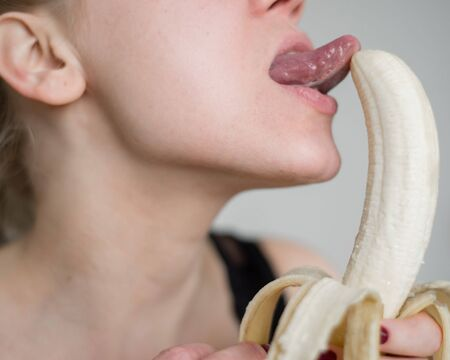 Close-up of the face, lips, tongue of a young, European girl licking a big yellow, sweet banana.