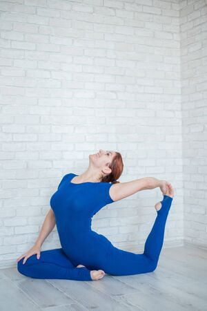 Red-haired woman in a blue jumpsuit practices yoga in a bright room. The girl sits in a pose of a pigeon, bends back Banco de Imagens